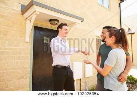 Real estate agent giving house keys to new property owners