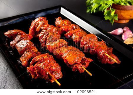 Pork skewers to grill and barbecue. Still life on black background