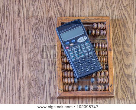 Old abacus and mathematical calculator lying on a wooden table poster