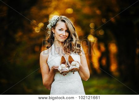 bride holding wedding shoes