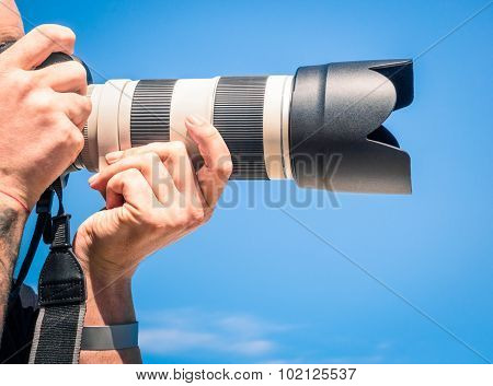Photographer outdoors with big zoom digital lens as professional equipment getting ready to shoot a photo poster