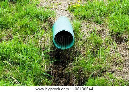 Plastic green drain pipe emerging from grassy ground. poster
