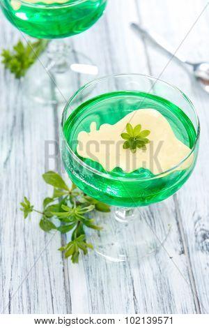 Portion of Woodruff Jelly with Vanilla Sauce on bright wooden background poster