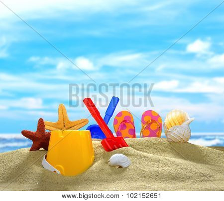 Children's flip flops with beach toys and seashells on the sandy beach poster