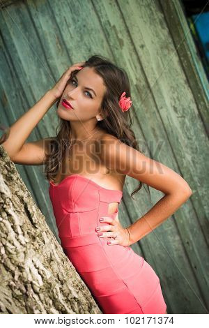 Girl in coral dress and flower barrette standing beside tree