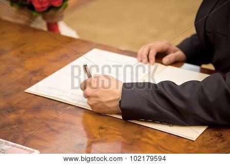 Marriage. Bridegroom puts his signature to the document poster
