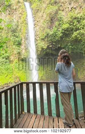 Woman talking on the phone at waterfall