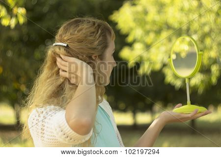 Young beautiful girl look into mirror in the park.Soft and blur conception