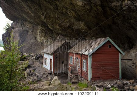 two houses of ancient settlement below rock Helleren Jossingfjord Stavanger Southern Norway poster