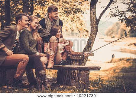 Cheerful friends in autumn park taking selfie