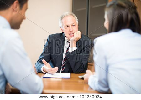 Businessman talking to a young couple