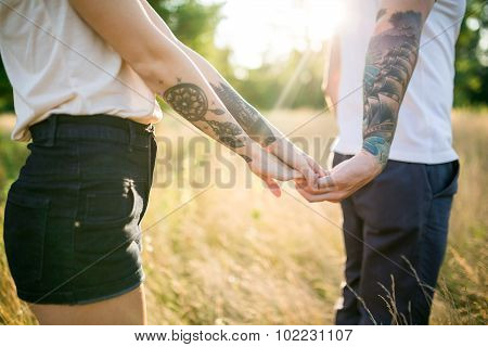A Man And A Girl With A Tattoo On The Nature Holding Hands