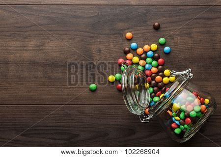 overturned glass jar full of colorful sweets