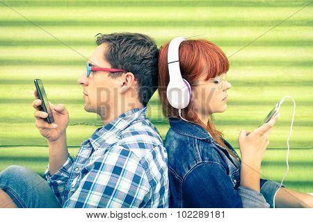 Hipster Couple In Disinterest Moment With Mobile Phones - Concept Of Apathy Sadness And Isolation