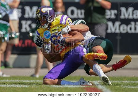 VIENNA, AUSTRIA - JUNE 22, 2014: WR Laurinho Walch (#6 Vikings) is tackled by S Sascha Verhoeven (#3 Dragons).