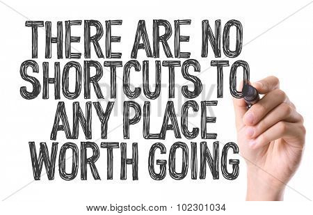 Hand with marker writing: There Are No Shortcuts To Any Place Worth Going