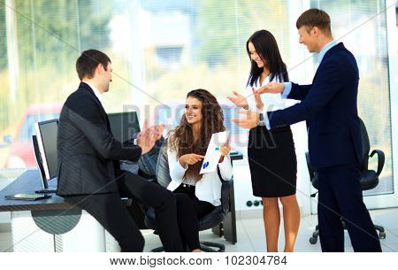 Young businesspeople clapping for female colleague after presentation poster