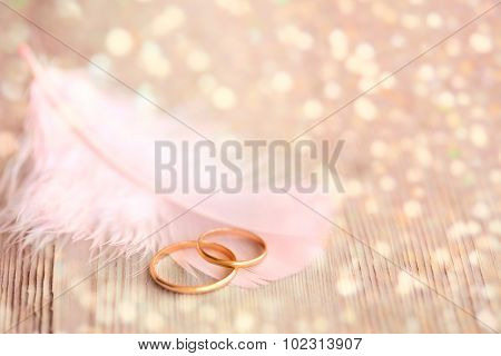 Wedding  Background with Gold Rings, pink feather and golden magical lights