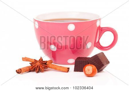 Big mug polka dot of tea with chocolate candy and filberts, isolated on white background