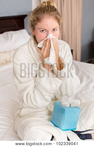 Young sick woman holding tissue sitting  in bed
