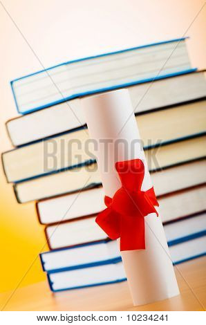 Diploma And Stack Of Books Against The Background