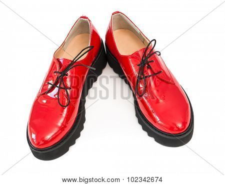 pair of red patent leather boots isolated on white background