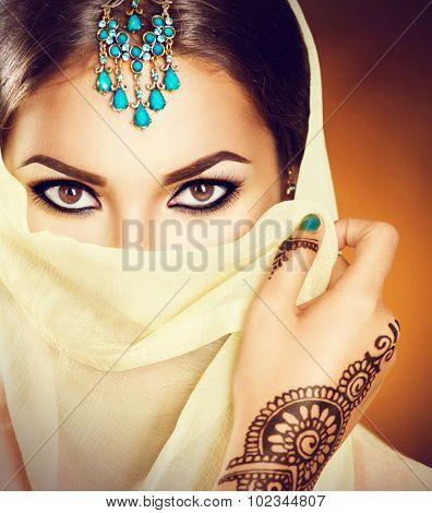 Beautiful Indian girl with traditional turquoise jewels hiding her face behind the veil. Young Hindu woman portrait with mehndi tattoos from black henna on hand. Beauty Arabian model looking at camera