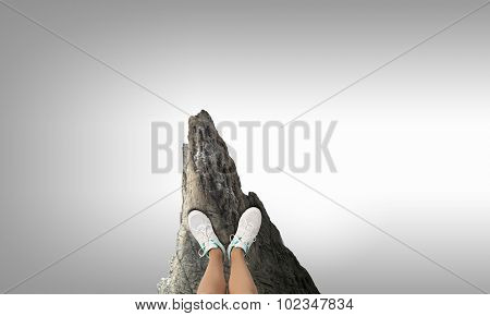 Close up of woman legs standing on the edge of rock