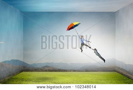 Man trying to catch another who flying on colorful umbrella