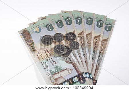 One thousand Dirham currency notes and coins on white background.