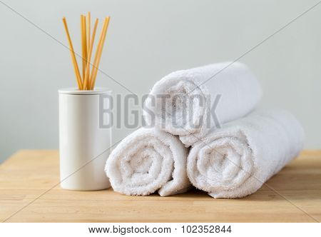 Aromatherapy reed diffuser air freshener with stack of white towel