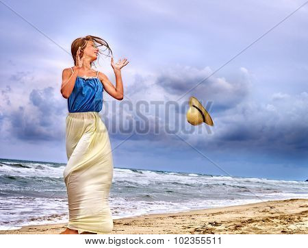 Summer girl sea.  Woman on coast near ocean with waves. Wind blew his hat.