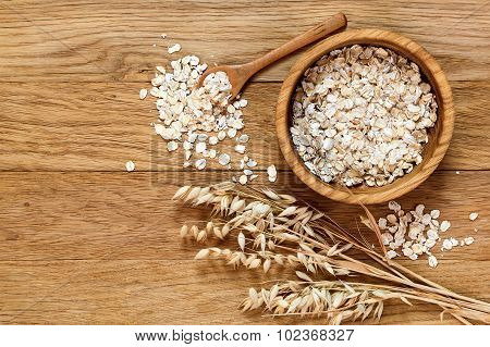 Rolled Oats And Oat Ears Of Grain On A Wooden Table