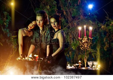 Beautiful Witches With The Vintage Book Of Magic. Night Forest On The Background.