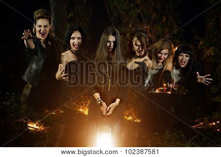 Six Beautiful Witches Are Looking At The Camera. Dark Forest On The Background.