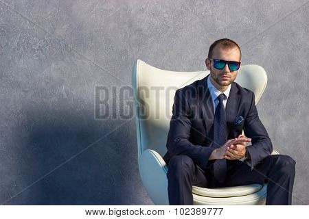 Brutal businessmen in suit with tie and sunglasses sitting on chair. Boss concept.