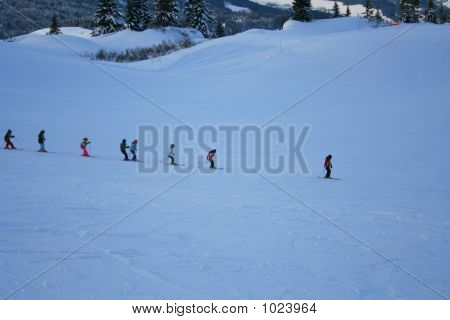 group of kids skiing down with instructor poster