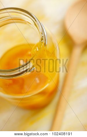 Yellow mirabelle plum jam blob over opened jar screw filled with jam. Shallow depth of field. poster