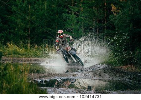 Motocross racer rides through a puddle