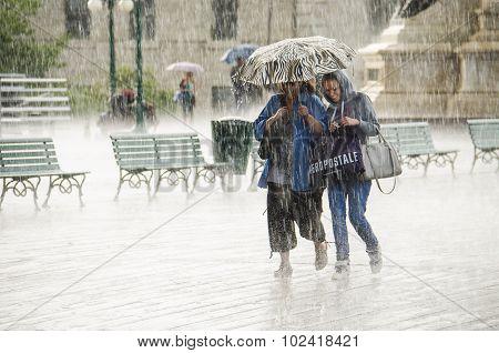 Two Women Walking under Umbrella during Heavy Rain