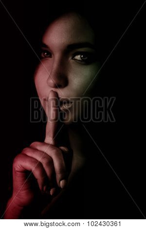 Shhh secret concept - woman with finger over lips