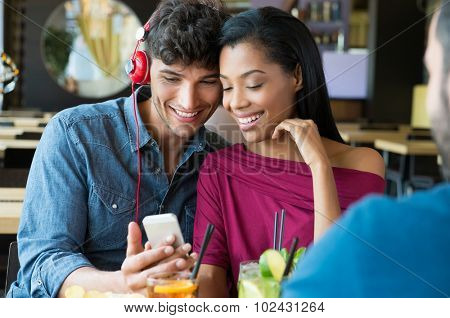 Closeup shot of young couple listening to music with mobile phone at coffee bar. Young man and african woman looking at smartphone at caf���©. Happy young couple listening music with headphones.