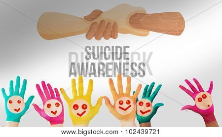 Hands with colourful smiley faces against suicide prevention message