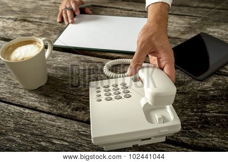 Business Person With Blank Paper And Cup Of Fresh Coffee Infront Of Him About To Make A Phone Call