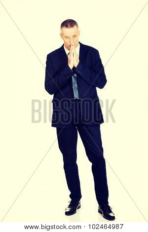 Hopeful businessman with clenched hands.