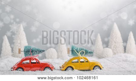 Miniature cars with fir tree on abstract background