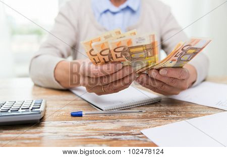 business, savings, annuity insurance, age and people concept - close up of senior woman with calculator and bills counting euro money at home