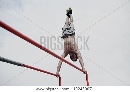 fitness, sport, training and lifestyle concept - young man exercising on parallel bars outdoors