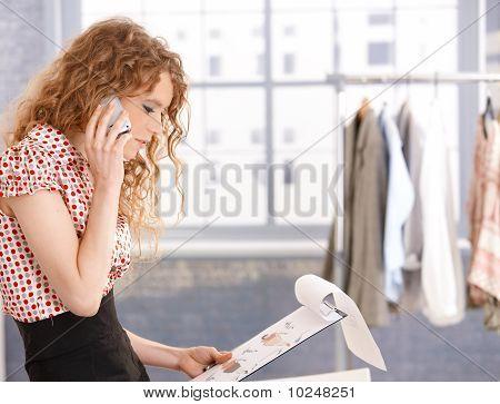 Pretty Fashion Designer In Work Using Mobile Phone