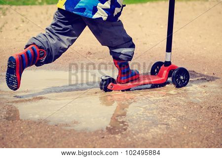 child playing in water puddle, kids outdoors